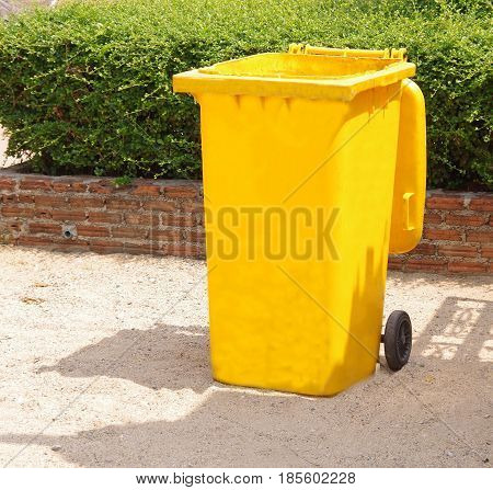 Yellow wheelie bin with open lid in the sun.
