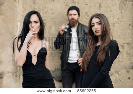 Sexy girl smoker with cigarette and pretty woman with long brunette hair in stylish black dress. Blurred handsome man or hipster with beard on grungy cement wall. Passive smoking