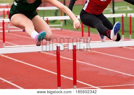 Two high school girls are dead even while racing the 100 meter high hurdles