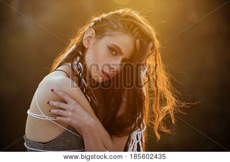 young pretty woman or sexy girl with rope in dreadlocks in long curly hair with fashionable makeup and piercing in nose has red lips on blurred natural background