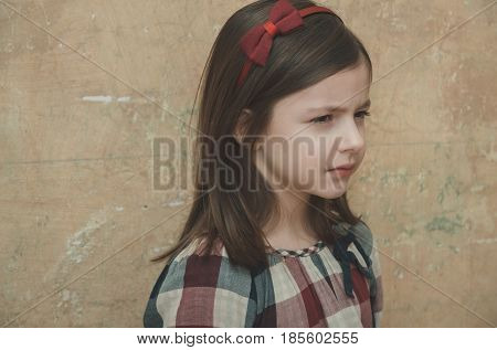 Childhood and fashion Cute small little girl child with adorable face and stylish headband with red bow in long brunette hair posing on beige wall.