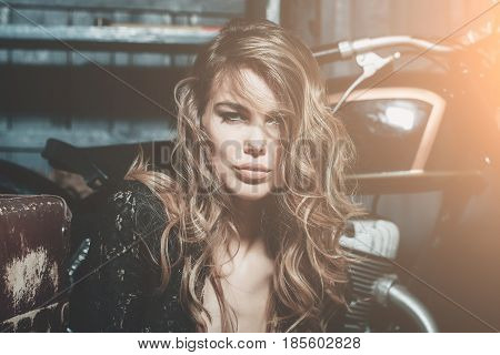 fashion model or beautiful woman and girl with pretty face makeup and stylish blond curly long hair sitting at metallized motorcycle on garage background. Motorcycling hobby and lifestyle
