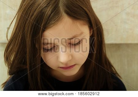 Sad cute pretty girl child kid with depress eyes on adorable face and long brunette hair sitting on beige background. Loneliness melancholy and boredom