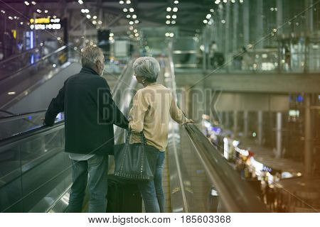 Lovely senior couple tourists on escalator