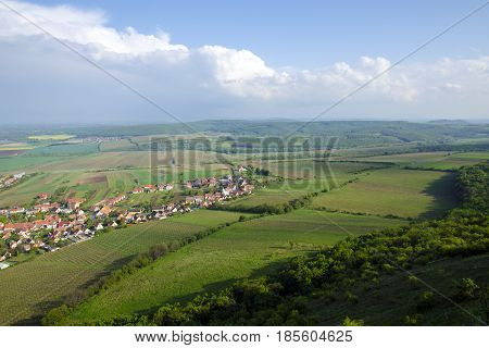 View of the village of Pavlov and the vineyards and fields in the area of Palava - South Moravia under a blue sky with clouds