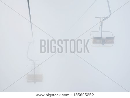 Chairlift In Foggy Mountains