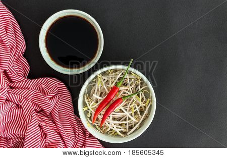 Red chili peppers on soybean sprouts in green bowl soy sauce in bowl and a striped towel on black background. Asian food concept.