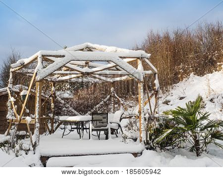 Gazebo with patio furniture and palm tree under the snow on a sunny day