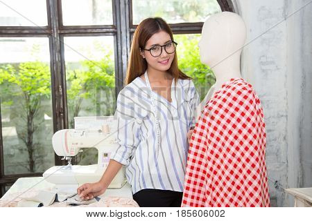 Young woman designer working at studio on garment on dressmaker's model