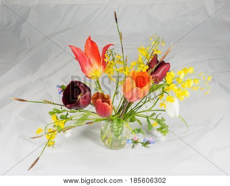 Bouquet of freshly cut spring flowers in a glass vase against crinkled white paper background