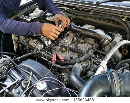 Car service engine repair check up maintenance auto mechanic man tightened valve under hood car people hand fixing car engine in garage workshopcheck up power engineafter servicemaintenance