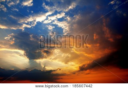 Multicolor sunset sky with storm clouds and sun rays above sea