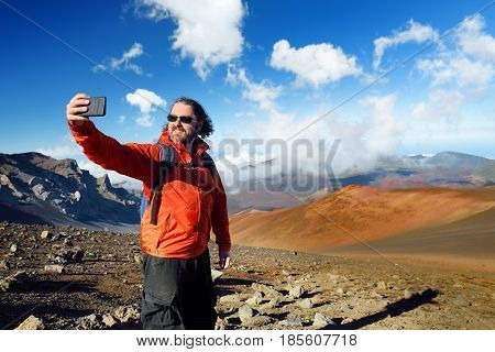 Tourist taking a photo of himself in Haleakala volcano crater on the Sliding Sands trail. Beautiful view of the crater floor and the cinder cones below. Maui Hawaii USA.
