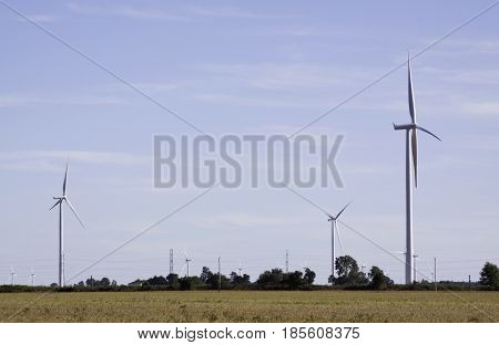 Close landscape view of multiple wind turbines in a farmer's field near Windsor, Ontario with the moon visible on a sunny late afternoon in September.
