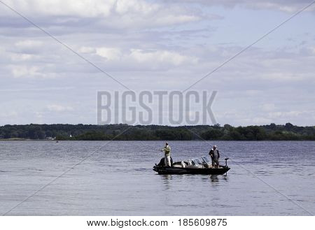 Notre Dame de Ile Perrot, Quebec - June 20, 2014 -- Wide landscape view of two men fishing from a small boat in Lac St-Louis in Notre Dame de Ile Perrot, Quebec with trees foliage in the background on a sunny day in June.