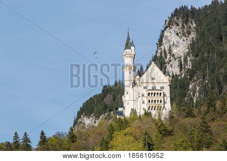 The famous Neuschwanstein Castle in Bavaria In the background flying skydiver on blue sky. Germany