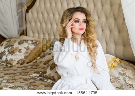 Beautiful seductive woman flirting with the camera sitting on a bed in White bathrobe looking up with a coquettish look.