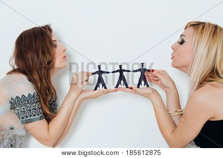 Two Girls Are Holding Paper People On A White