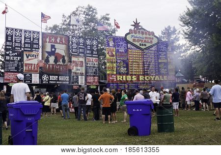 Cornwall, Quebec - July 26, 2014 - Wide view of the colorful billboard signs and crowds of people lined up for food at the Ribfest in Cornwall, Ontario on a sunny afternoon in July.