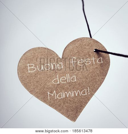 closeup of a brown cardboard heart strung on a string with the text buona festa della mamma, happy mothers day written in italian, against an off-white background