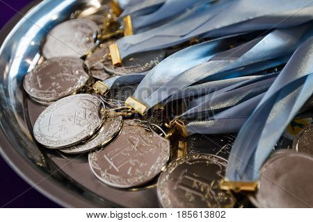 Many silver medals with blue ribbons on a silver tray awards of champions sport achievements second place prize for the winner