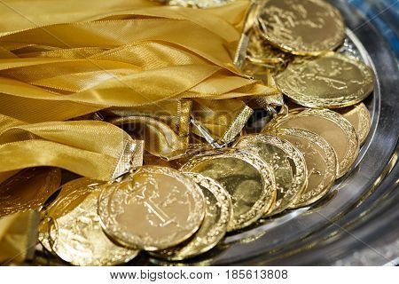 A lot of gold medals with yellow ribbons on a silver tray awards of champions sport achievements first place prize for the winner