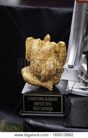Cornwall, Quebec - July 26, 2014 - Vertical of a trophy for the Best Chicken displayed at the Ribfest in Cornwall, Ontario on a sunny afternoon in July.