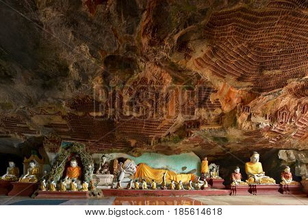 Beautiful panoramic view inside Kawgun Cave Hpa-An Myanmar (Burma). Lots of Buddha statues and ancient stucco on walls.