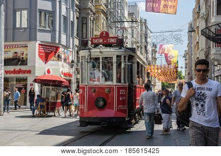ISTANBUL TURKEY - JUNE 26 2015: A red classic tram in the crowded Istiklal street in the Beyoglu district of Istanbul Turkey. It is the most famous street in Istanbul