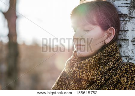 Portrait Of A Beautiful Girl With A Bang. She Stands Leaning Against The Tree Trunk With Her Eyes Cl