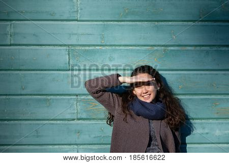 Asian Girl Is Standing By The Wall And Screwing Up Her Eyes Because Of The Bright Sun. She Smiles An