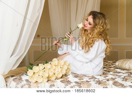 Beautiful seductive woman flirting with the camera is sitting on the bed with a big bouquet of white roses in White bathrobe looking up with a coquettish look.