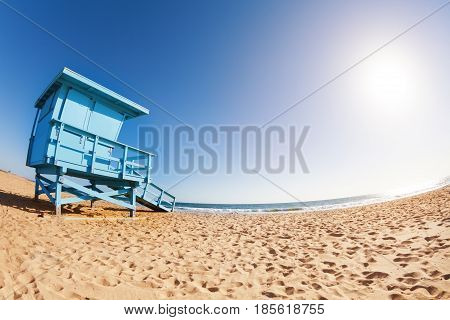 Fisheye shoot of deserted sea shore with blue wooden lifeguard tower at sunny day