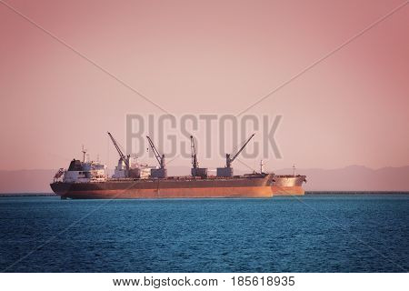 Two bulk carriers with cranes loading cargo at sunset off the coast of Long Beach, California