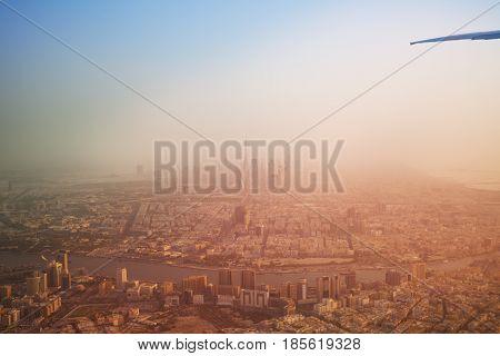 Overlooking beautiful Dubai skyline in haze through aircraft window