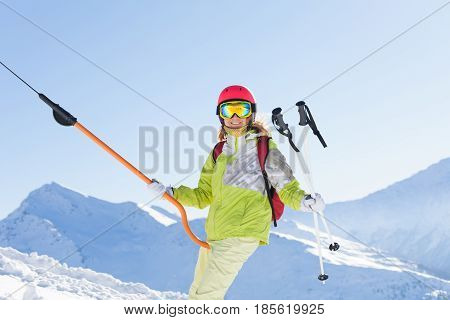Portrait of smiling young woman in ski suit lifting on button lift at sunny snowy day