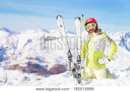 Portrait of female skier in diving mask and snorkel standing on knees in snow bank against beautiful mountain scene