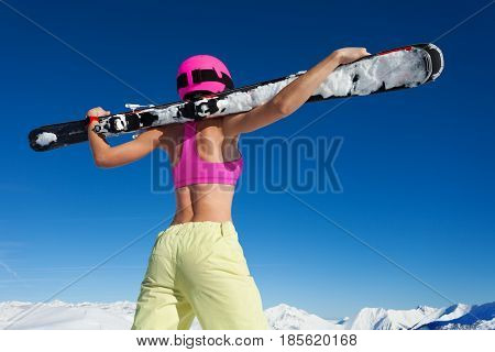 Back view picture of girl in pink helmet with skis in outstretched arms underhand against of snowy mountains in sunlight