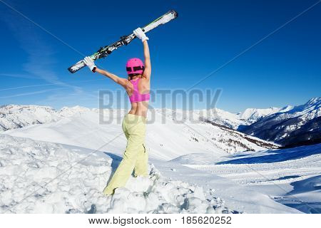 Back view portrait of topless female skier with skies in outstretched arms above head against of snowy mountains