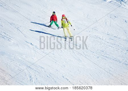 Two skiers, young woman and her kid son  hitting the slopes at snowy mountains