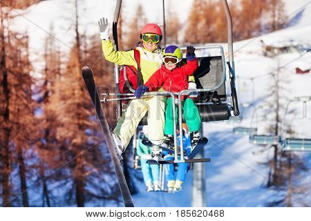 Happy skiers, mother with her kid lifting on chairlift and waving hands