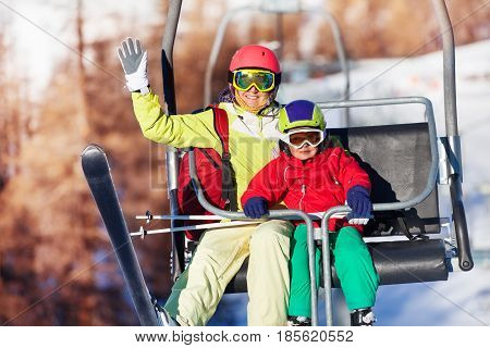Close-up portrait of happy young woman and her son lifting on chairlift at mountains waving hand
