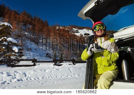 Happy young woman having rest after skiing sitting in opened car trunk and drinking warm tea