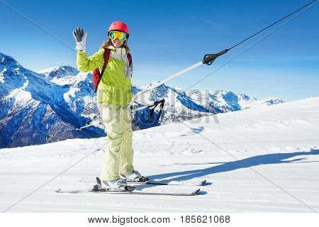 Happy young woman on a button ski lift going uphill and waving hand against beautiful mountain scene