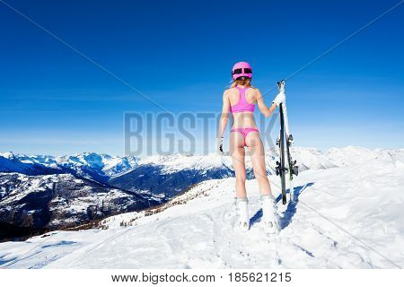 Back view portrait of sporty girl in pink bikini with skies on the snowy mountain peak