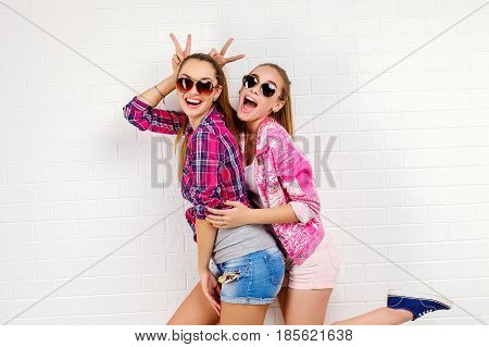 Fashion portrait of two friends posing. modern lifestyle.two stylish sexy hipster girls best friends ready for party.Two young girl friends standing together and having fun. Looking at camera.