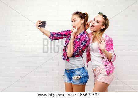 Fashion portrait of two friends posing. modern lifestyle.two stylish sexy hipster girls best friends ready for party.Two young girl friends standing together and having fun. Taking selfie