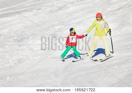 Active mother teaching her son to make the stem turn, skiing holding hands at snowy mountains