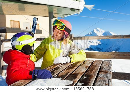 Young woman and her kid son having rest, sitting at the table in the mountain cafe after skiing outdoors