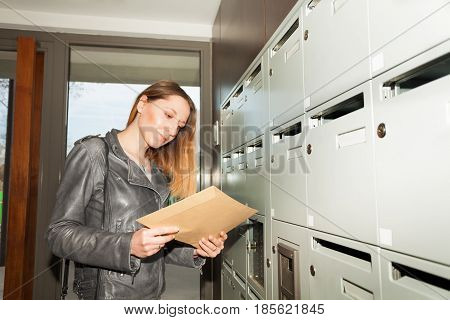 Young woman holding envelope standing next to the mailboxes in the hall